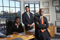 An in office portrait of three business executives, An African American man and woman, and an Hispanic man. The office wall is adorned with many plaques and awards.