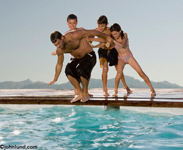 Picture of three young children pushing their father into the swimming pool on a warm sunny day. Picture of family fun by the swimming pool. Leisure and lifestyle images for advertising.