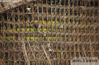 Stock photo of a bridge under construction in China. Laborers carry sacks of cement up the bamboo scaffolding of this huge structure.