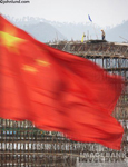 Picture of the Chinese flag waving in front of bridge and highway construction in a stock photo about China's growth and development.