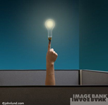 A light bulb balancing on the tip of a finger that protrudes up an beyond a cubicle office.