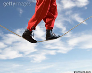 A man's legs walking on a tight rope against a lightly clouded blue sky and symbolizing challenge, bravery, skill and accomplishment.