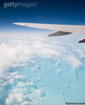 The wing of a commercial jet flying over a tropical ocean tens of thousands of feet below. Deep dark blue sky above the horizon.