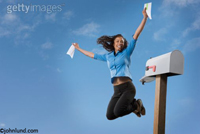 A happy smiling and very excited woman is jumping high into the air in front of her mail box presumably because she has received good news.