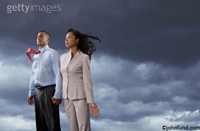 A couple faces into a storm in this concept stock showing teamwork, determination and togetherness. The storm clouds gather darkly behind them while his tie and her hair are whipped by the winds of change.