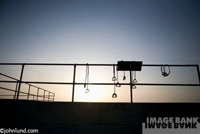 Outdoor still life of exercise equipment at dawn in the San Francisco Bay Area. The equipment is silhouetted by the rising fiery hot ball of the sun.