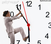 Woman holding back the hands of time, stopping time and staying in the present moment. A businesswoman is hanging on to the minute hand of a giant clock trying to stop time from advancing.