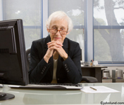 Picture of a mature woman at her office desk exuding confidence and well-being. The older female executive has her hands clasped together in front of her chin. She is looking at the camera over the top of her glasses.