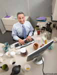 Pictures of Businessman in a cubicle with too much coffee. The man is surrounded by empty and half empty coffee cups, coffee pots etc.