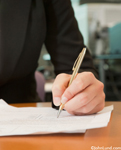 A Senior woman's hand signs a document in this concept stock photo illustrating sealing the deal and agreement. Picture of older woman signing documents with a cross pen. One hand holding pen writing on paper.