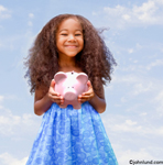 Picture of a young black girl happily holding her piggy bank with a wonderful smile and lots of hair. She is wearing a bright blue dress and the blue sky is the background. The girl has big hair.