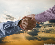 Picture of a strong firm handshake. Against a bold sunrise two hands clasp each other in a firm handshake denoting agreement, teamwork and alliance. The shaking hands separate the sky background into a bright sky above and cloudy sky below the arms.