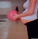 Picture of a pregnant woman holding a bowling ball preparing to roll the ball to a strike.  The woman's blouse does not entirely cover her baby bump, which also resembles the bowling ball.