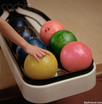 Picture of bowling balls, green,pink,orange,and gold. A human hand is picking up the gold colored ball.