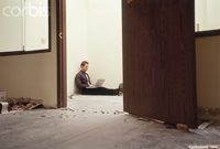 Photograph of a man sitting on the floor with a computer on his lap. The secen is one of commercial space being remodeled.