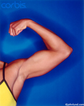 Strong woman's biceps set against a dark blue background.  The woman is wearing a yellow tank top. Picture cropped to show only arm and shoulder.