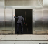 An executive businessman looking down an elevator shaft in suprise and dismay. Photo of a malfunctioning elevator in a business office.  The walls around the elevator are all stainless steel. Small business advertising picture.