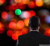A businessman is seen from behind as he faces numerous red lights and one green light. Black man waiting for the light to change at a crosswalk.