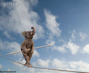 Funny animal and stock photo of an elephant walking upright (anthropomorphic) on a tightrope demonstrating unexpected skill, agility and balance.