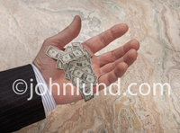 A hand of a businessman holds a pile of tiny dollars in a corporate environment illustrating micro payments, loans, cash flow and banking issues.