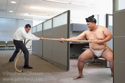 Photo of a Sumo wrestler engaged in a tug of war with a businessman in an office of cubicles: A funny stock picture of a Sumo Wrestler.