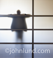 Picture of a man, behind a frosted glass partition, feeling overwhelmed and in need of a break.