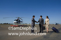 Asian business people meeting and shaking hands at the heliport near a helicopter.  Two Asian businessmen and an Asian woman businessperson with their luggage at the airport.