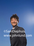 Smiling young Asian business executive outdoors with a deep blue sky for the background. Asian business person photo.