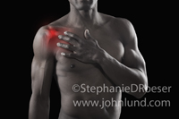 An African American man, sans shirt, holds his aching and painful shoulder. The pain and discomfort is shown with a red glow around the barely visible joint structure.