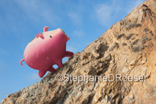 A piggy bank breaks out in beads of sweat as he climbs a steep hill in a photo about sweat equity, investment and finance.