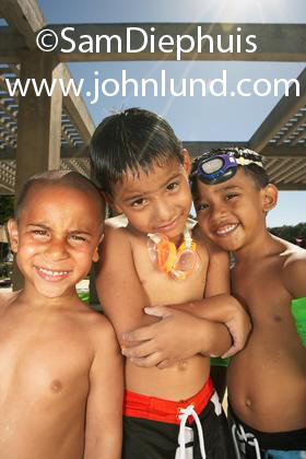 Three young Hispanic boys are standing by each other smiling at the camera posing for a portrait. They are wearing their swimsuits and two have swim goggles on. Happy kids having fun on summer vacation.