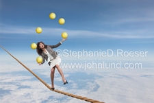 Photo of a woman struggling with her balance on a tightrope while juggling oversized yellow balls, all at an extremely high altitude!