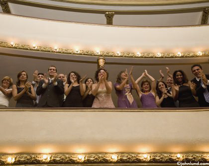 A theater audience in a balcony gives an enthusiastic standing ovation.