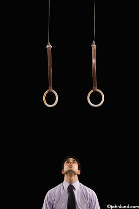 A businessman looks up with determination at gymnastic rings hanging above him symbolizing goal setting, ambition, challenge and possibility.