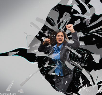 A business woman shattering a glass barrier. Angry looking woman with balled up fists is smashing through the glass barrier.