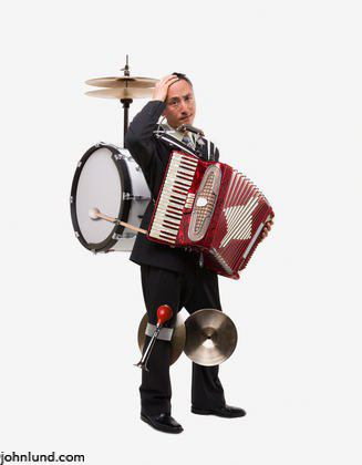 A one man band stands exhausted from the effort to keep up with it all in a humorous stock photo.