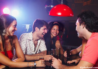 Picture of young people in a nightclub. Two couples are sitting around a table in a disco club having some brews and having a good time with each other.  Attractive young people partying hard.