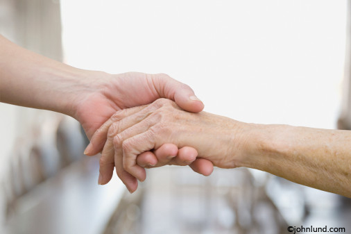 Middle aged hand holding an elderly person's hand, Tender loving care expressed through touch. Represents, human qualities like kindness, empathy, compassion, love and more.