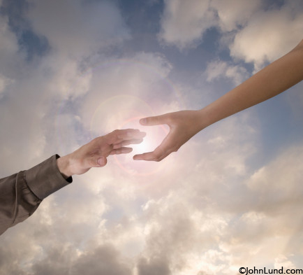 Two hands reach for each other through a dramatic sky with the sun positioned behind in an image about connection, teamwork and offering a helping hand.