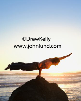 Beach photo of a man doing a one armed balancing act with his body in a horizontal position. The sun is setting behind him. Bare chested man at the beach doing acrobatic stuff.