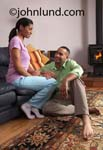 Stock photo of a black couple at home in their living room relaxing and talking. She is sitting on the couch or sofa with him sitting on the floor. He is barefoot and resting his hand on her leg. He is smiling up at her.