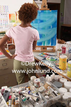 Picture of a black woman artist painting a picture in her art studio.  A slender African American woman artist is painting a picture with her back to the camera.  The female artist in the photo is wearing a pink blouse and studying her painting.
