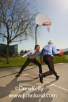 Picture of two business executives playing a game of pick up basketball outdoors on a bright sunny day. Businessmen in suits playing basketball without thier coats.  Senior executive playing with junior executive on the basketball court.