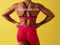 Photo of a black woman body builder from behind. Strong woman flexing back muscles. Picture of a healthy fit African American woman body builder flexing her muscles. Bodybuilder lifestyle ad pics.