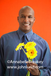 Stock picture of a man holding bright yellow flowers in his hand and smiling at the camera. Handsome bald black man in a blue dress shirt and tie is holding a bouquet of yellow flowers in his hand. The background is orange.