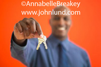 Picture of a black man holding out a set of house keys.  The smiling african american man is out of focus and the house keys he is handing to someone are in focus. Turning over the keys photo. Advertising pics for real estate, home buying, and other uses.