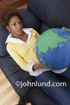Picture of a black woman holding a world globe in her hands. The African American woman is laying back in a relciner and she is wearing a yellow sweater over a white blouse. Ad pics for travel.