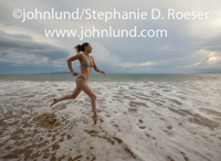 Stock picture of a baby boomer woman running on the beach as part of her fit and healthy lifestyle even while on a tropical vacation in Hawaii.