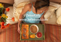 Picture of a woman eating breakfast in bed in the morning. The woman is in bed with a tray of breakfast food. Pics of breakfast in bed. She has a bowl of cereal, half of a pink grapefruit, and a glass of orange juice.