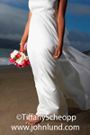 Picture of a bare foot bride walking on the beach in a beautiful white wedding dress and holding a bouquet of flowers in one of her hands. Image cropped to mid-chest down.